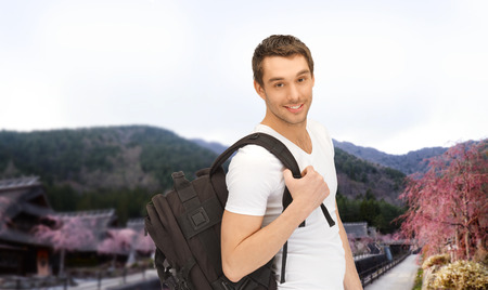 people travelling: people, travel, tourism and education concept - happy young man with backpack and book travelling over asian landscape background