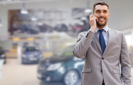 telephone salesman: auto business, car sale, gesture and people concept - smiling businessman talking on smartphone over auto show background