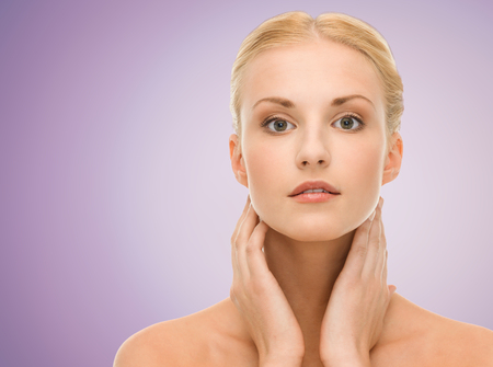 woman neck: beauty, people and health concept - beautiful young woman with bare shoulders over violet background Stock Photo