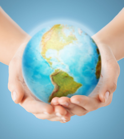 hands holding earth: people, geography, population and peace concept - close up of human hands with earth globe showing american continent over blue background