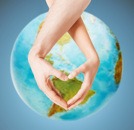 people, peace, love, life and environmental concept - close up of human hands showing heart shape gesture over earth globe and blue background photo