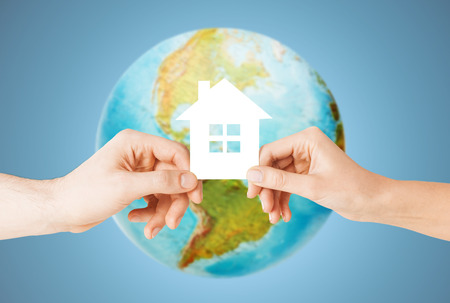 people, home, ecology and land resources saving concept - closeup of woman and man hands holding green paper house over earth globe and blue background photo