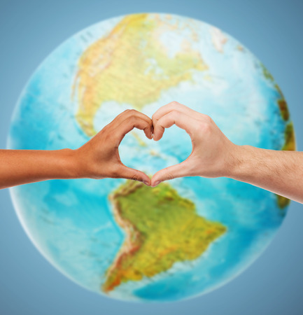people, peace, love, life and environmental concept - close up of human hands showing heart shape gesture over earth globe and blue background