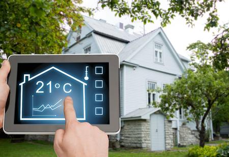 ahorro energia: casa, vivienda, las personas y la tecnología concepto - cerca de las manos del hombre que señala el dedo a la computadora Tablet PC y regulan la temperatura ambiente a lo largo de fondo casa