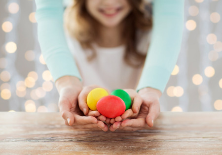easter, family, people, holiday and childhood concept - close up of happy girl and mother hands holding colored eggs over lights background photo