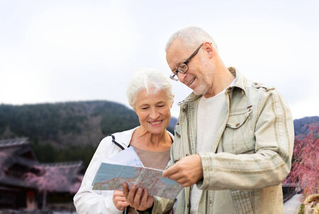 family, age, tourism, travel and people concept - senior couple with map and over asian village and mountains landscape background photo