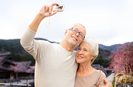 tourism: age, tourism, travel, technology and people concept - senior couple with camera taking selfie over asian village landscape background Stock Photo