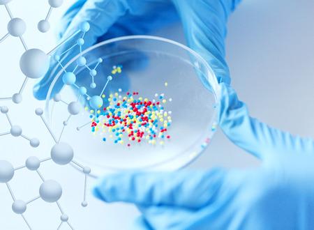 la ciencia, la química, la biología, la medicina y la gente concepto - cerca de científico o médico manos sosteniendo placa de Petri con cápsulas químicos química en el laboratorio