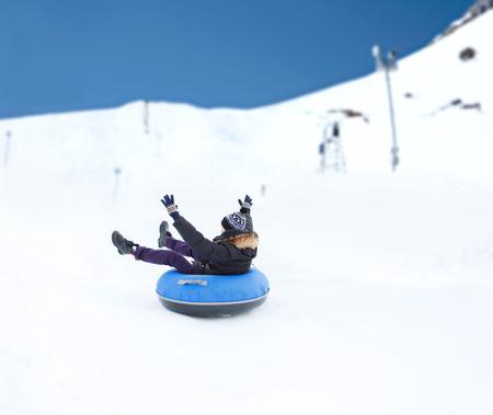 hombres jovenes: invierno, el ocio, el deporte, y la gente concepto - adolescente feliz o joven desliz�ndose por el tubo de nieve sobre fondo de la monta�a Foto de archivo