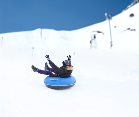 tubes: winter, leisure, sport, and people concept - happy teenage boy or young man sliding down on snow tube over mountain background
