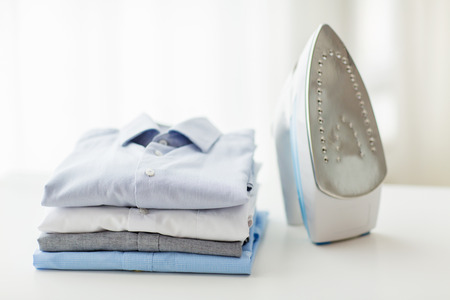 laundry concept: ironing, clothes, housework and objects concept - close up of iron and clothes on table at home