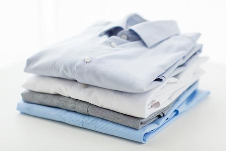 lavanderia: plancha, lavandería, ropa, limpieza y objetos concepto - cerca de camisas planchadas y dobladas sobre la mesa en casa