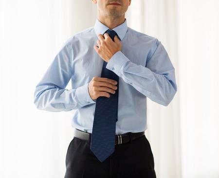 corpo umano: persone, affari, moda e abbigliamento concetto - close up di uomo in camicia vestirsi e regolazione cravatta sul collo a casa