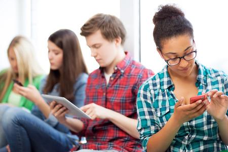colegios: tecnolog�a e internet concepto - los estudiantes que buscan en los tel�fonos y Tablet PC en la escuela Foto de archivo