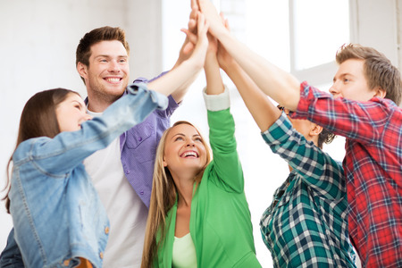 education and friendship concept - happy students giving high five at school