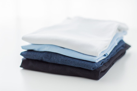 ironing, laundry, clothes, housekeeping and objects concept - close up of ironed and folded t-shirts on table at home Stock Photo