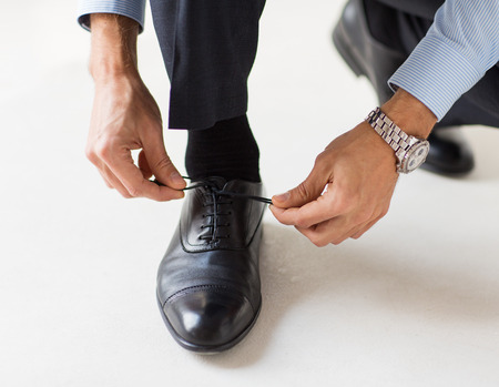 office shoes: people, business, fashion and footwear concept - close up of man leg and hands tying shoe laces