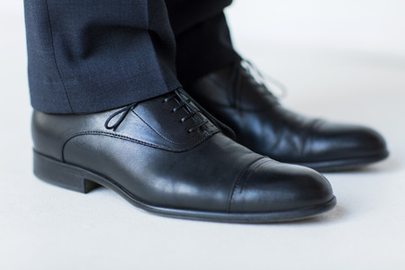 people, business, fashion and footwear concept - close up of man legs in elegant shoes with laces or lace boots 版權商用圖片