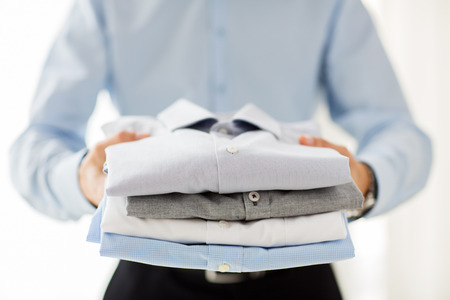 folded clothes: business, clothing and people concept - close up of businessman holding folded shirts