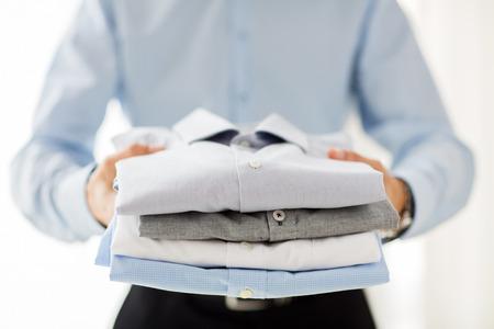vestidos: los negocios, la ropa y la gente concepto - cerca de negocios la celebración de camisas dobladas