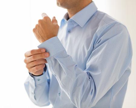 mensen, bedrijven, mode en kleding concept - close-up van de mens bevestiging knoppen op mouw thuis Stockfoto