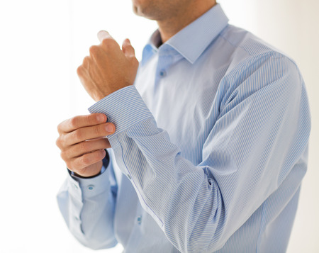 putting up: people, business, fashion and clothing concept - close up of man fastening buttons on shirt sleeve at home