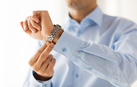 fastening: people, business, accessories and clothing concept - close up of man in shirt fastening wristwatch at home