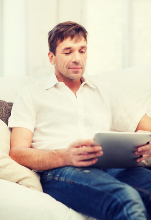 new age: technology and lifestyle concept - handsome man working with tablet pc at home