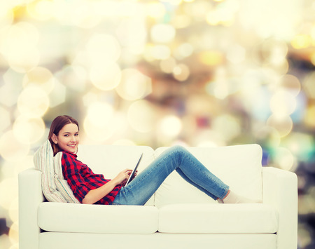 technology and happy people concept - teenage girl sitting on sofa with tablet pc Stock Photo