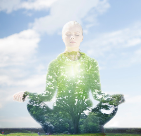 sport, fitness, yoga, double exposure and people concept - happy young woman meditating in lotus pose over blue sky and green tree background Foto de archivo