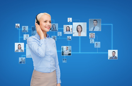 business, communication, cooperation and people concept - happy female helpline operator with headset over blue background and icons of contacts or customers Stock Photo