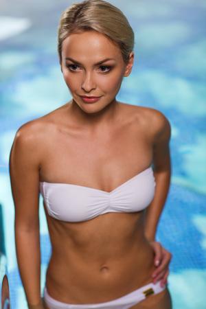 Menschen, Schönheit, Spa, gesunden Lebensstil und Entspannung Konzept - schöne junge Frau in Bikini-Badeanzug Anhebung oben im Schwimmbad Standard-Bild - 36669424