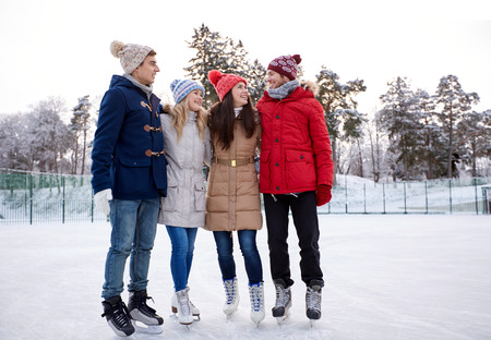 people, winter, friendship, sport and leisure concept - happy friends ice skating and hugging on rink outdoors photo