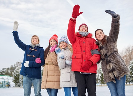 people, winter, friendship, sport and leisure concept - happy friends waving hands on ice rink outdoors photo