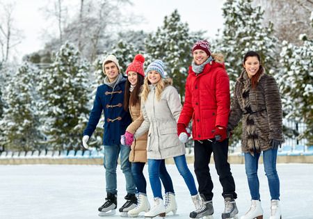 ice skating: people, winter, friendship, sport and leisure concept - happy friends ice skating and holding hands on rink outdoors