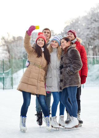 people, friendship, technology and leisure concept - happy friends taking selfie with smartphone on ice skating rink outdoors photo