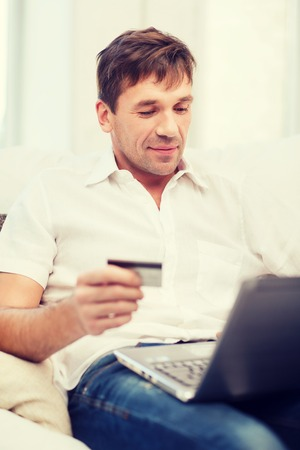 online or internet shopping concept - smiling man with laptop and credit card at home photo