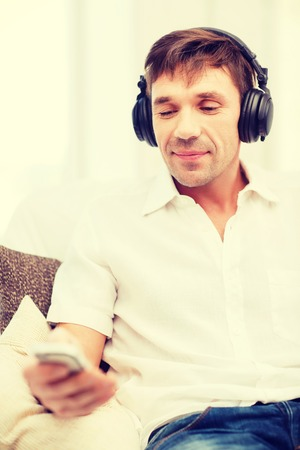 new age music: technology, leisure and lifestyle concept - happy man with headphones listening to music at home