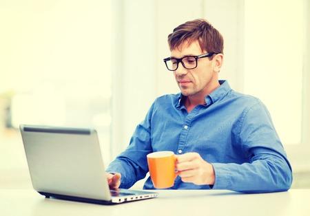 技術、ビジネス、ライフ スタイルのコンセプト - 温かいお茶やコーヒーのカップを保持している、自宅でラップトップを扱う眼鏡の男