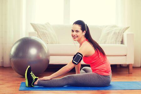 armband: fitness, sportm casa e il concetto di dieta - sorridente ragazza con execising bracciale a casa Archivio Fotografico