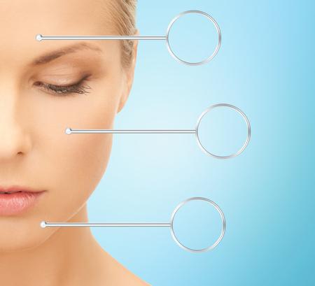 mensen, huidverzorging en schoonheid concept - close-up van mooie jonge vrouw half gezicht over blauwe achtergrond Stockfoto