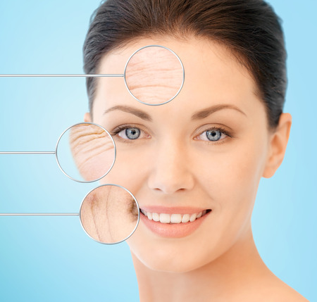female face closeup: people, skin care and beauty concept - face of beautiful happy young woman over blue background