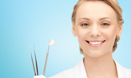 stomatologist: people, medicine, stomatology and healthcare concept - happy young female dentist with tools over blue background Stock Photo