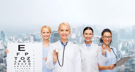 eye exam: healthcare, vision and medicine concept - smiling female eye doctors and nurses with eye exam chart, glasses and clipboard