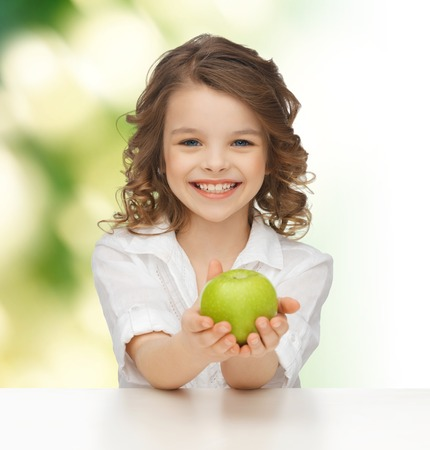 people, healthy food, children and happiness concept - happy girl with green apple over green background