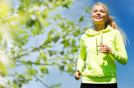 healthy person: fitness, people and healthy lifestyle concept - happy young female runner jogging outdoors Stock Photo
