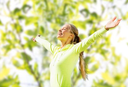 fitness, deporte, la felicidad y el concepto de la gente - mujer levantando las manos felices sobre el árbol de hojas verdes de fondo
