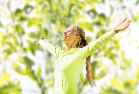 fitness, sport, happiness and people concept - happy woman raising hands over green tree leaves background