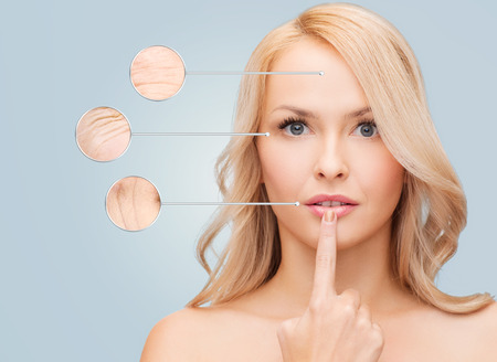 aging skin: health, people and beauty concept - beautiful young woman touching her lips over blue background