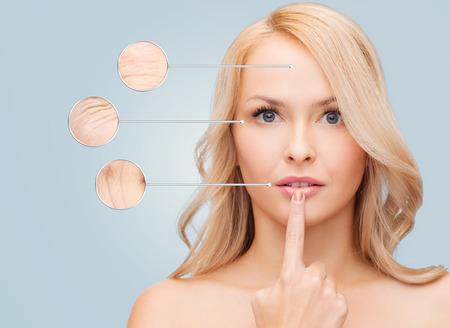 arrugas: la salud, las personas y el concepto de belleza - mujer hermosa joven que toca sus labios sobre fondo azul